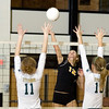 Record-Eagle/Keith King<br /> Traverse City Central's Katie Fallick, middle, hits the ball as Traverse City West's Tayler Rodes, left, and Courtney VanHouzen, right, jump to defend Tuesday, November 2, 2010 at Traverse City Central High School.