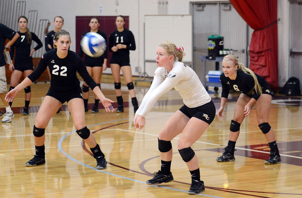 . Butte College\'s #8 Mikaela Woodbury (center) takes a dig as #22 Courtney Robinson (left) and #6 Lacie Landrum (right) look on against Chico State in their volleyball game at CSUC Acker Gym Saturday, August 24, 2013 in Chico, Calif.  (Jason Halley/Chico Enterprise-Record)