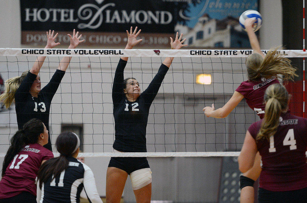 . Butte College\'s #13 Emilie Aase (left) and #12 Callie Flood (center) attempt to block against Chico State\'s #4 Hannah Wilkins (right) in their volleyball game at CSUC Acker Gym Saturday, August 24, 2013 in Chico, Calif.  (Jason Halley/Chico Enterprise-Record)