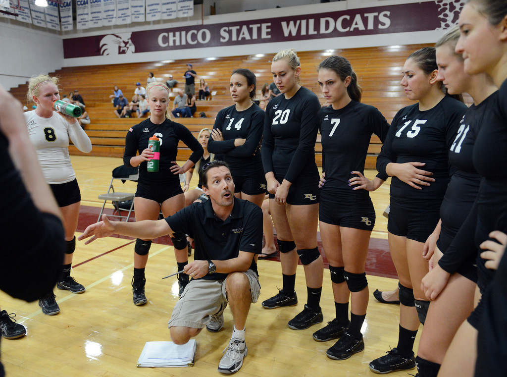 . Butte College coach Dave Davis (center) talks to #8 Mikaela Woodbury, #6 Lacie Landrum, #14 Gabby Delarosa, #20 Erika Click, #7 Taylor Johnson, #15 Kristen Keys, #21 Drew Tattam and others (left to right) against Chico State in their volleyball game at CSUC Acker Gym Saturday, August 24, 2013 in Chico, Calif.  (Jason Halley/Chico Enterprise-Record)