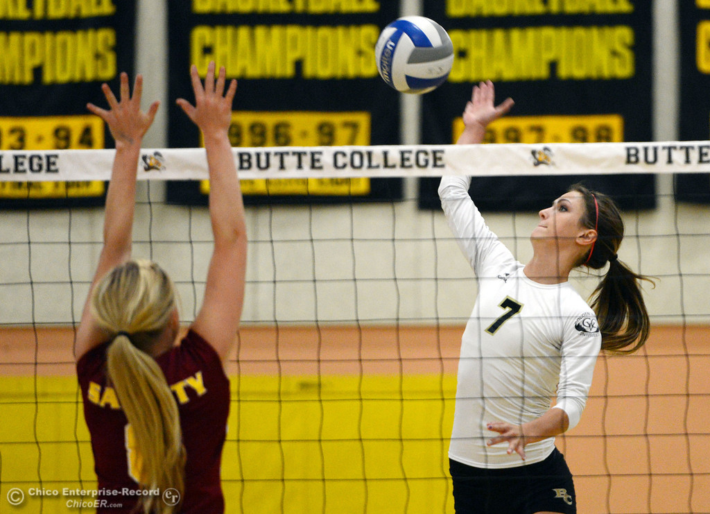 . Butte College\'s #7 Taylor Johnson (right) spikes against Sac City College\'s #8 Kylee Hardy (left) in the first game of their women\'s volleyball match at Butte\'s Cowan Gym Wednesday, September 25, 2013, in Oroville, Calif.  (Jason Halley/Chico Enterprise-Record)