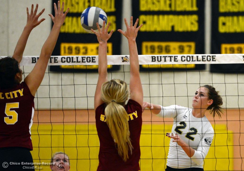 . Butte College\'s #22 Courtney Robinson (right) spikes against Sac City College\'s #8 Kylee Hardy (center) and #15 Raven Balafoutis (left) in the first game of their women\'s volleyball match at Butte\'s Cowan Gym Wednesday, September 25, 2013, in Oroville, Calif.  (Jason Halley/Chico Enterprise-Record)