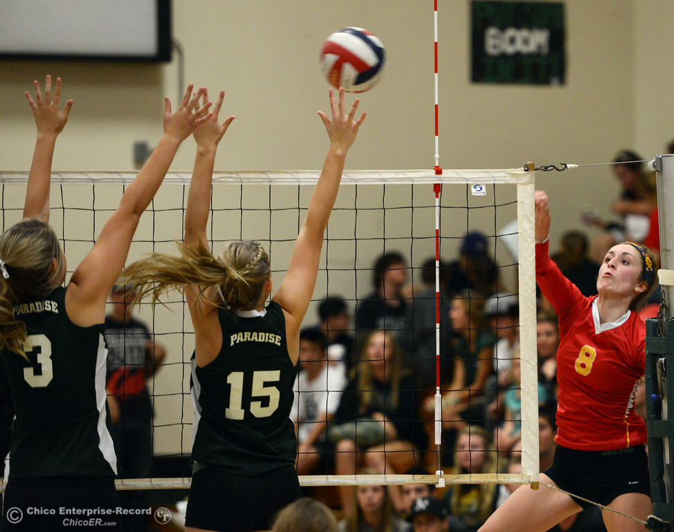 . Chico High\'s #8 Emma Contreras (right) spikes against Paradise High\'s #15 Emilee Heinke (center) and #3 Kelsi Earhart (left) in the second game of their girls volleyball match at PHS Thursday, October 10, 2013 in Paradise, Calif.  (Jason Halley/Chico Enterprise-Record)