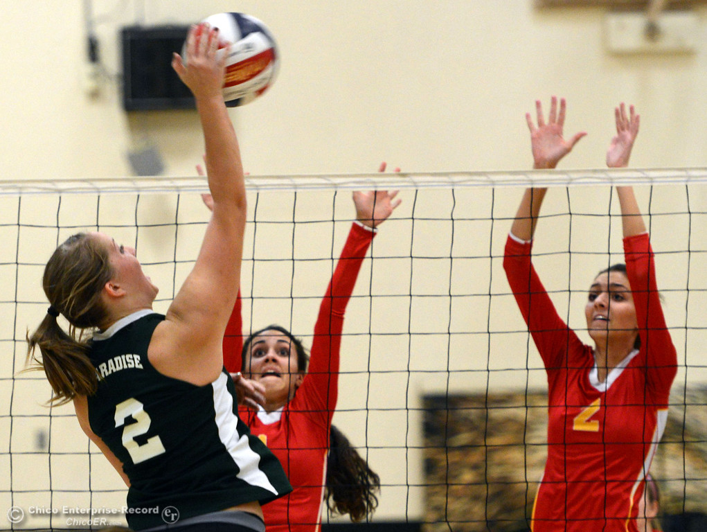 . Paradise High\'s #2 Bailey Bengson (left) spikes the ball against Chico High\'s #1 Cia Seibert (center) and #2 Sydney Gaskey (right) in the second game of their girls volleyball match at PHS Thursday, October 10, 2013 in Paradise, Calif.  (Jason Halley/Chico Enterprise-Record)