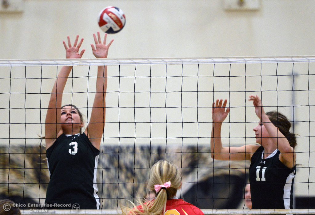 . Chico High\'s #13 Becca Korte (center) spikes against Paradise High\'s #3 Kelsi Earhart (left) and #11 Jennifer Olson (right) in the first game of their girls volleyball match at PHS Thursday, October 10, 2013 in Paradise, Calif.  (Jason Halley/Chico Enterprise-Record)