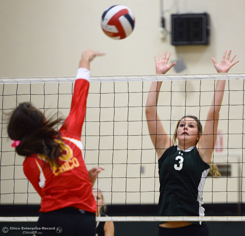 . Chico High\'s #13 Becca Korte (left) spikes against Paradise High\'s #3 Kelsi Earhart (right) in the first game of their girls volleyball match at PHS Thursday, October 10, 2013 in Paradise, Calif.  (Jason Halley/Chico Enterprise-Record)