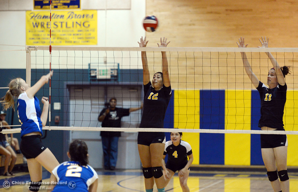 . Hamilton High\'s #1 Nicole Gordon (left) spikes against Gridley High\'s #12  Lauren Solis (center) and #11 Elizabeth Osbourn (right) in their second game of their volleyball match Thursday, August 29, 2013 in Chico, Calif.  (Jason Halley/Chico Enterprise-Record)