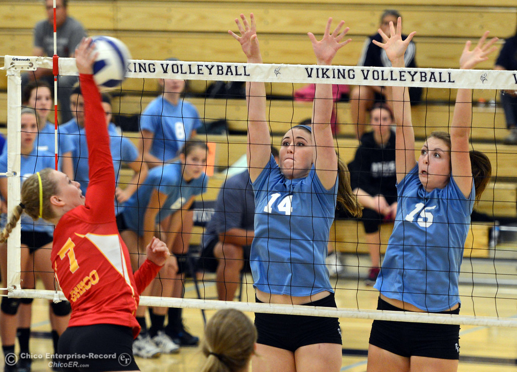 . Chico High\'s #7 Allysa Barrett (left) spikes the ball against Pleasant Valley High\'s #14 Courtney Holloway (center) and #15 Sydney Stanley (right) in the first game of their girls volleyball match at PVHS Varley Gym Saturday, October 12, 2013 in Chico, Calif.  (Jason Halley/Chico Enterprise-Record)
