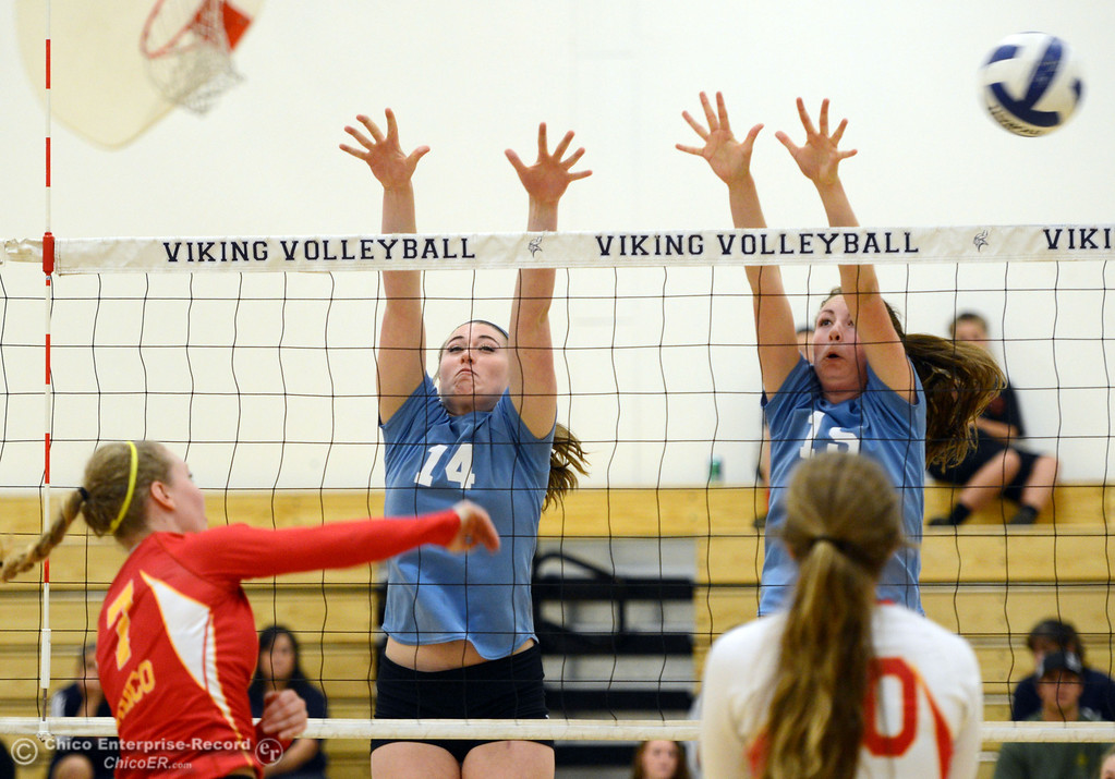 . Chico High\'s #7 Allysa Barrett (left) spikes against Pleasant Valley High\'s #14 Courtney Holloway (center) and #15 Sydney Stanley (right) in the first game of their girls volleyball match at PVHS Varley Gym Saturday, October 12, 2013 in Chico, Calif.  (Jason Halley/Chico Enterprise-Record)