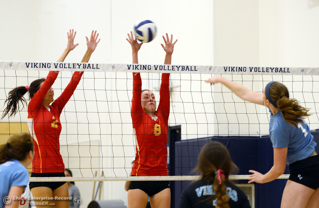 . Pleasant Valley High\'s #11 Heather Pemebroke (right) spikes against Chico High\'s #8 Emma Contreras (center) and #2 Sydney Gaskey (left) in the second game of their girls volleyball match at PVHS Varley Gym Saturday, October 12, 2013 in Chico, Calif.  (Jason Halley/Chico Enterprise-Record)