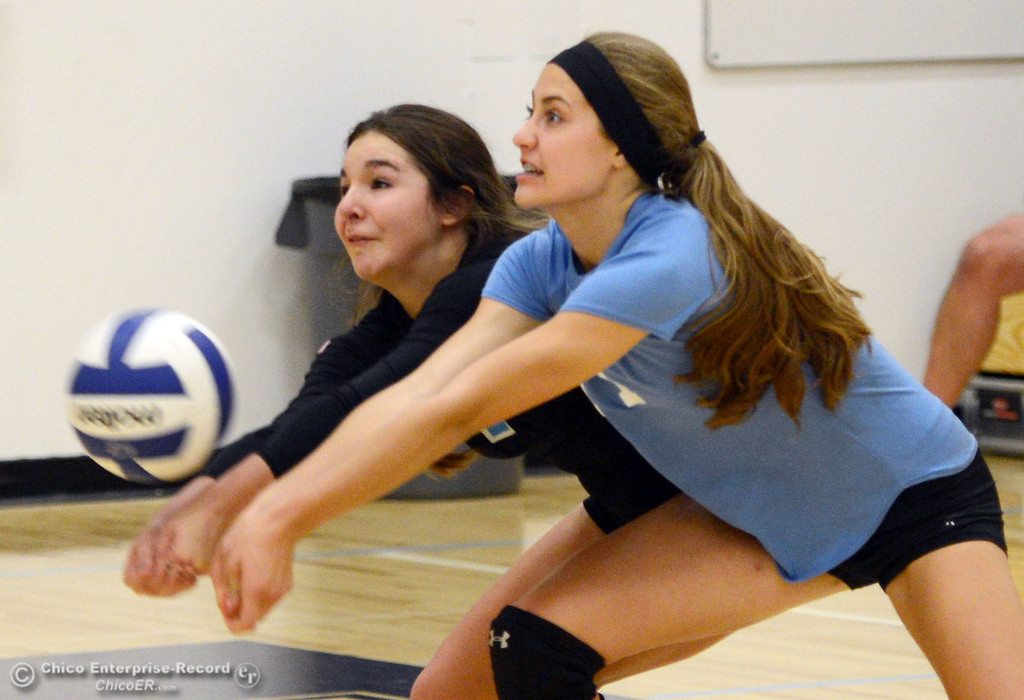 . Pleasant Valley High\'s #1 Brooke Fogel (left) and #11 Heather Pemebroke (right) both go in for a dig against Chico High in the second game of their girls volleyball match at PVHS Varley Gym Saturday, October 12, 2013 in Chico, Calif.  (Jason Halley/Chico Enterprise-Record)