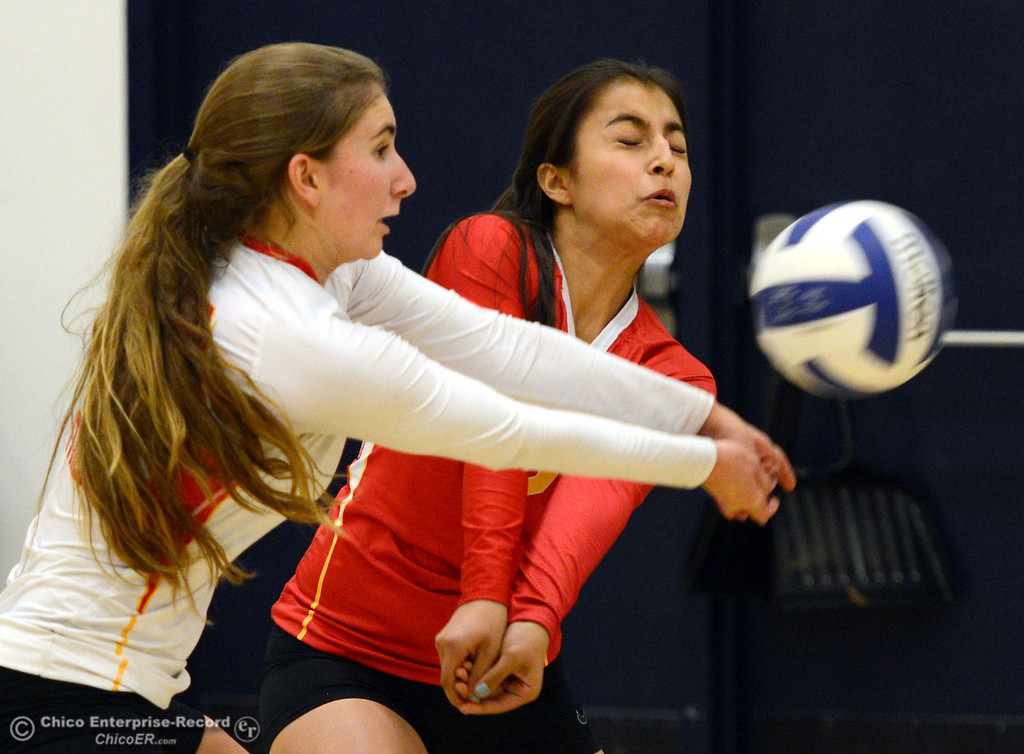 . Chico High\'s #10 Stacey Jones (left) and #6 Dahlia Chavez (right) go in for a dig against Pleasant Valley High in the second game of their girls volleyball match at PVHS Varley Gym Saturday, October 12, 2013 in Chico, Calif.  (Jason Halley/Chico Enterprise-Record)