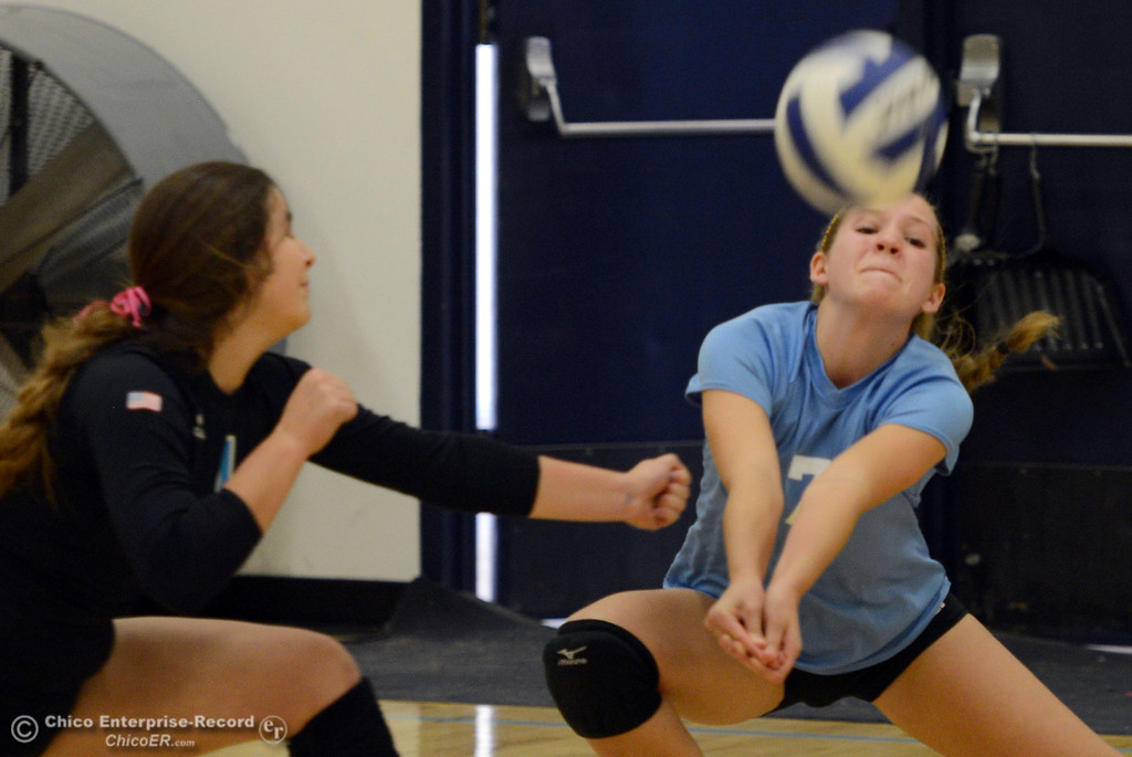 . Pleasant Valley High\'s #1 Brooke Fogel (left) and #7 Meagan Mason (right) go for a dig against Chico High in the first game of their girls volleyball match at PVHS Varley Gym Saturday, October 12, 2013 in Chico, Calif.  (Jason Halley/Chico Enterprise-Record)