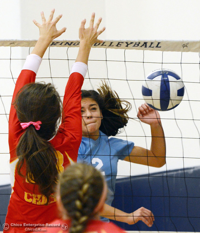 . Pleasant Valley High\'s #2 Lily Justine (right) spikes against Chico High\'s #13 Becca Korte (left) in the first game of their girls volleyball match at PVHS Varley Gym Saturday, October 12, 2013 in Chico, Calif.  (Jason Halley/Chico Enterprise-Record)