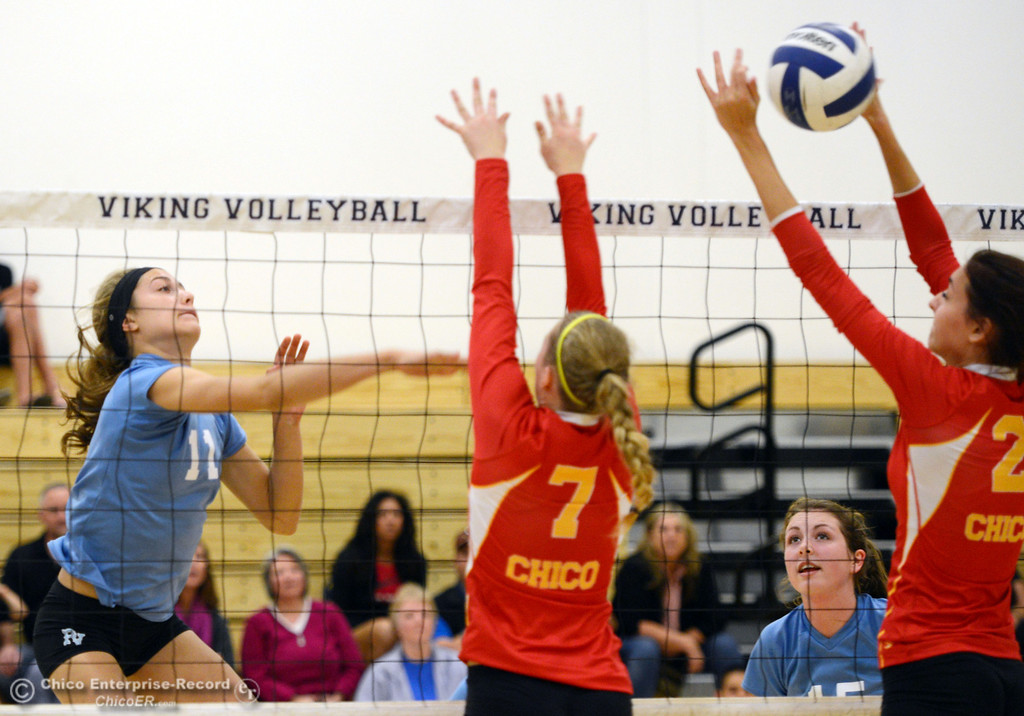 . Pleasant Valley High\'s #11 Heather Pemebroke (left) spikes against Chico High\'s #7 Allysa Barrett (center) and #2 Sydeny Gaskey (right) in the first game of their girls volleyball match at PVHS Varley Gym Saturday, October 12, 2013 in Chico, Calif.  (Jason Halley/Chico Enterprise-Record)