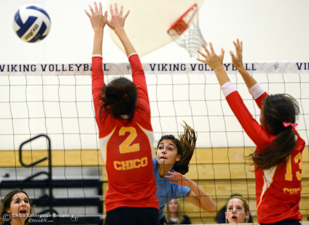 . Pleasant Valley High\'s #2 Lily Justine (center) spikes against Chico High\'s #2 Sydney Gaskey (left) and #13 Becca Korte (right) in the first game of their girls volleyball match at PVHS Varley Gym Saturday, October 12, 2013 in Chico, Calif.  (Jason Halley/Chico Enterprise-Record)