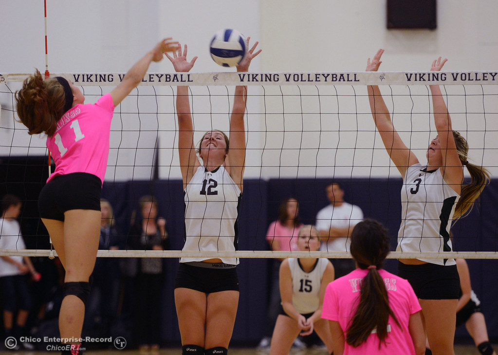 ". Pleasant Valley High\'s #11 Heather Pembroke (left) spikes against Paradise High\'s #12 Mariah Mundt (center) and #3 Kelsi Earhart (right) in the second game of their volleyball match at PVHS Varley Gym Thursday, October 17, 2013 in Chico, Calif. PV volleyball wore pink instead of blue vs Paradise at ""Fight Like a Viking Night,\"" to raise money for cancer research. (Jason Halley/Chico Enterprise-Record)"