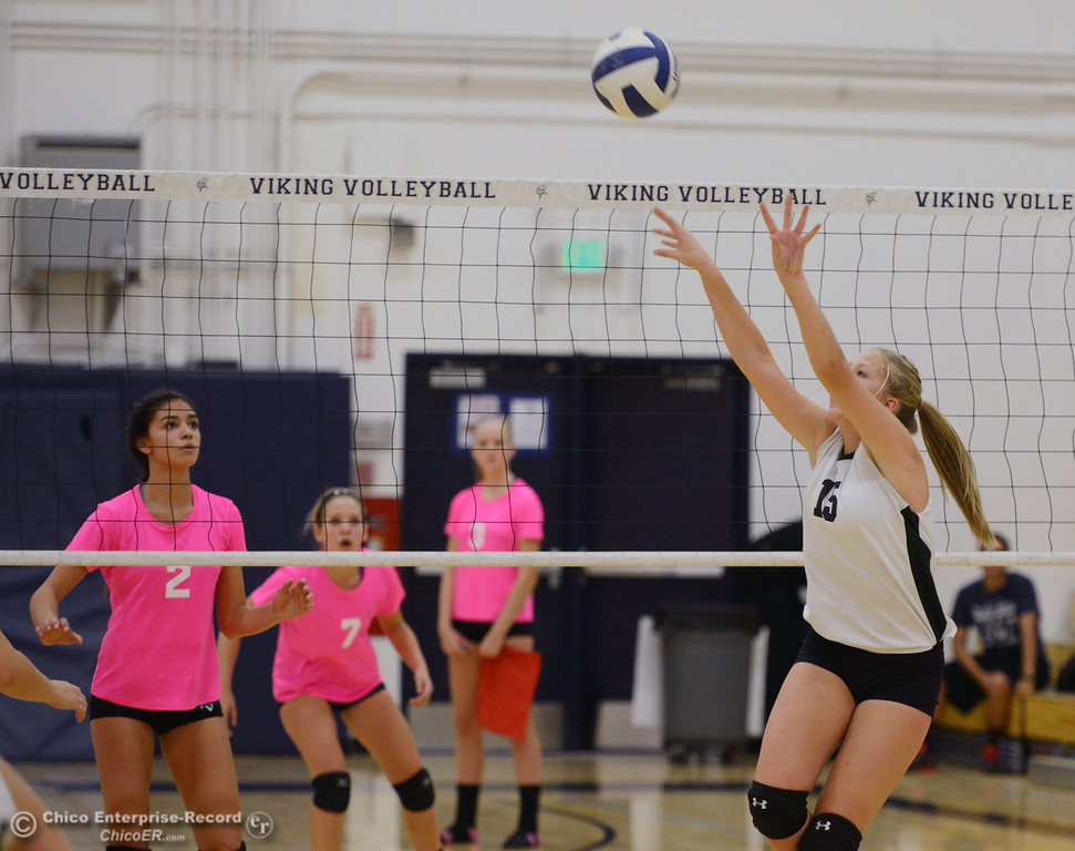 ". Paradise High\'s #15 Emilee Heinke (right) sets the ball against Pleasant Valley High in the second game of their volleyball match at PVHS Varley Gym Thursday, October 17, 2013 in Chico, Calif. PV volleyball wore pink instead of blue vs Paradise at ""Fight Like a Viking Night,\"" to raise money for cancer research. (Jason Halley/Chico Enterprise-Record)"