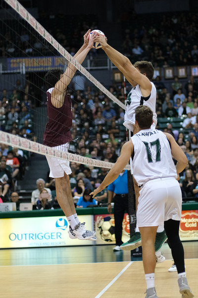 Hawaii middle Max Rosenfeld (13) jousts with a Charleston player in an opening night match at the Stan Sheriff Center in Honolulu, Hawaii on January 3, 2020.