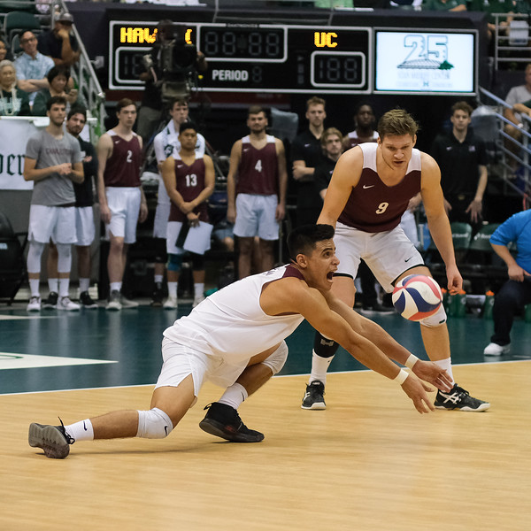 Charleston libero Edgar Sanchez makes a play for the ball as teammate Maarten Bartels (9) looks on in an opening night match against Hawaii at the Stan Sheriff Center in Honolulu, Hawaii on January 3, 2020. Sanchez had 3 digs for Charleston.