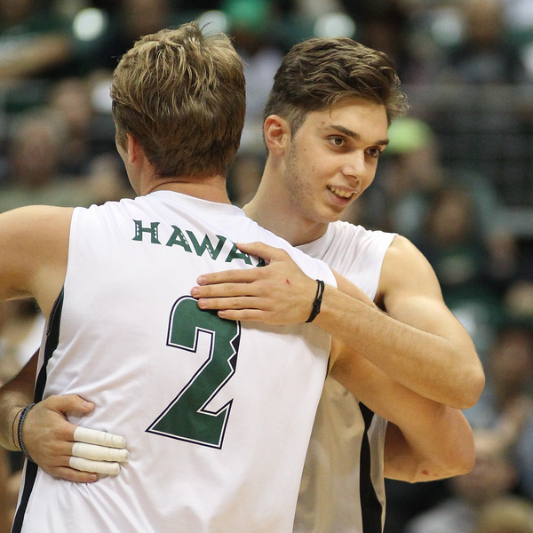 James Anastassiades (2) of Hawaii embraces freshman Dimitrios Mouchlias as he checks into the game for the first time in an opening night match against Charleston at the Stan Sheriff Center in Honolulu, Hawaii on January 3, 2020. Mouchlias, a 6-6 opposite/middle from Soufli, Greece, had 4 kills, hit .429, and added an ace in limited action.