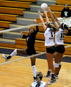 North Cobb's outside hitter Deanna Waller (8) tips the ball over Lauren Hutchinson (1) and Mariah Booth (10) of Kennesaw Mountain High School Saturday morning.