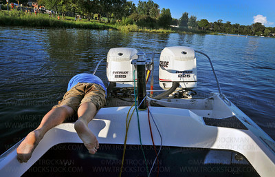 Shakopee-Prior Lake Shockwaves Water Ski Team boat driver Nat Svela pulls weeds from near the twin Evinrude 225 motors to enable his speedometer to work during the Wednesday evening, Aug. 11, 2010, performance.
