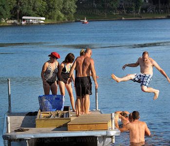 Shockwaves skier Joel Swanson, right, doing a split leap over fellow skiers below as the team erected their dock at Parkers Lake Park in Plymouth Wednesday evening, Aug. 10, 2011.