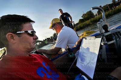Paul McGinty, left, holds the act order on a clipboard.  McGinty is typically a main skier and barefooter in the Shockwaves show, but had surgery on his thumb the day before after breaking it in the ski teams' Hoyt Lakes show.  Behind McGinty is Kent Johnson the teams' Ski Nautique boat driver, and on the dock is Tim Fitzgibbons getting ready for more barefoot action.