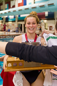 Brittany Sinclair with the trophy (Jenn Brennings arm handing a T-shirt to another player in the foreground)