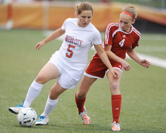 Globe/T. Rob Brown<br /> Webb City's Brittany Thurlo drives the ball as Carl Junction's Callie Degani looks for an opening Monday evening, April 8, 2013, at Webb City High School's field.