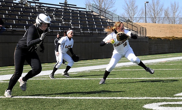 Gustavus Adolphus College's kailey Morgan throws to second base to turn a double play after fielding a bunt by St. Olaf's Jenn Boudreau (left) during their first game Thursday at Hollingsworth Field.