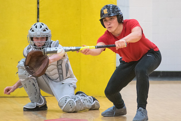 Mankato East's Kawika Hashimoto (right) practices bunting during practice in the East gymnasium. Hashimoto is a returning senior outfielder for the Cougars. Photo by Jackson Forderer
