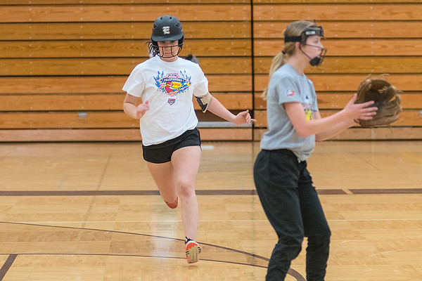 Makenzie Hendley (left) of Mankato East runs to second base during an indoor practice at the East gymnasium on Friday. Photo by Jackson Forderer