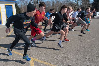 Mankato Loyola/Cleveland boys and girls track coach Dale Compton (left) starts his runners on a series of sprints during practice in the Loyola parking lot on Thursday. The track teams have been practicing in the parking lot and in the gymnasium due to the late seasonal snow. Photo by Jackson Forderer