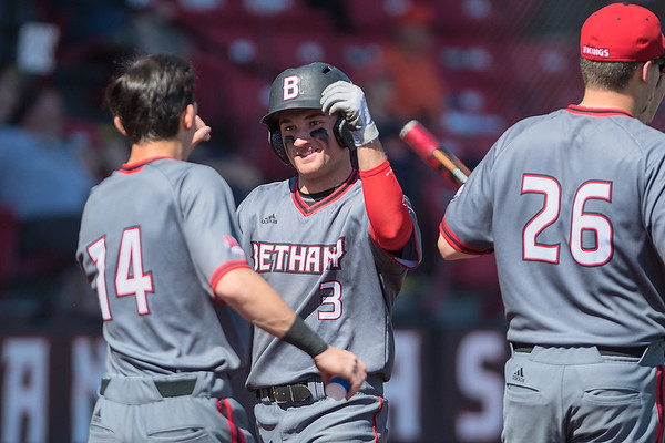 Bethany Lutheran's Ross Beumer (3) is congratulated by teammate Conner Side after scoring a run against Northland College during Saturday's double header. Bethany scored 36 total runs in their lopsided wins over the Jacks. Photo by Jackson Forderer