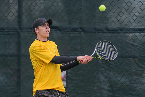 Mankato East's Koby Gagnon hits a backhand in the No. 1 doubles match against Mankato West on Thursday. Photo by Jackson Forderer