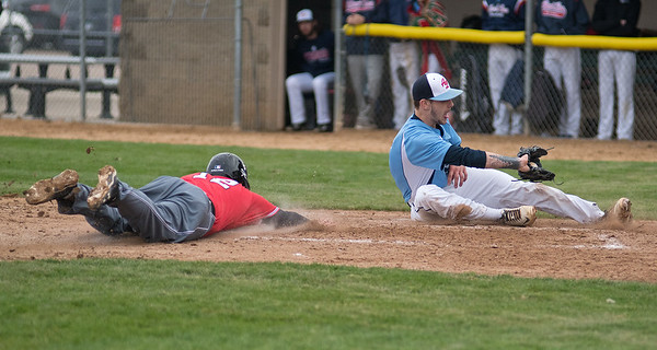 Jackson Schwartz (12) of Mankato West slides into home plate ahead of a tag from Albert Lea's pitcher Blake Simon after a wild pitch was thrown in Thursday's conference game played at Franklin Rogers Park. Photo by Jackson Forderer