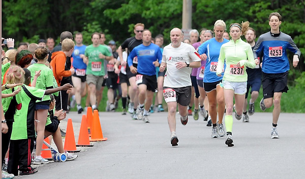 Runners are cheered on near the start of Saturday's 7 at 7 trail race at Seven Mile Creek park.