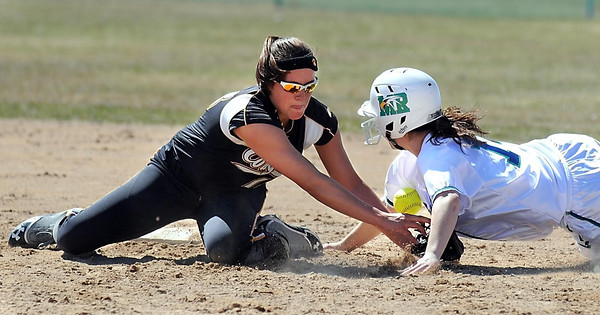 Mankato East's Savannah Quandt has the ball knocked out of her glove by a sliding Maple River's Molly Landsteiner during a game Saturday at Caswell Park.
