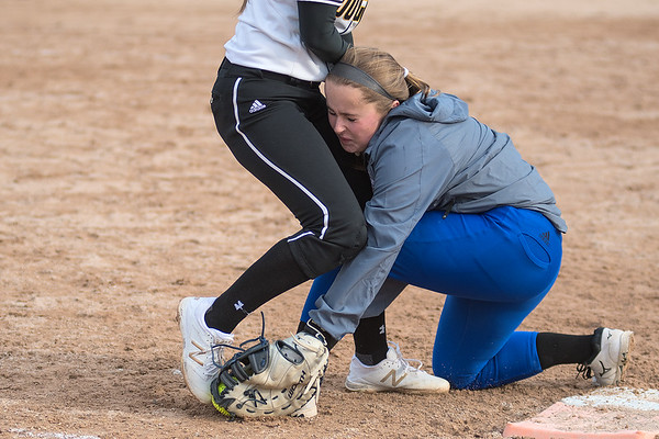 Lily Andrego of Mankato East collides with Owatonna's Hannah Fisher while trying to reach first base. The Cougars won both games of their doubleheader against Owatonna. Photo by Jackson Forderer