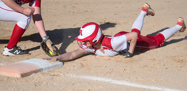 Austin's Jordyn McCormack slides safely back to first base from a tag put on by Mankato West's Brooke Pahl. The Scarlets defeated Austin 7-5. Photo by Jackson Forderer
