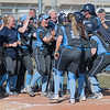 The Upper Iowa softball team surrounds teammate Erin Drahozal after her three-run home run tied the game against Minnesota State at five in the sixth inning. Photo by Jackson Forderer