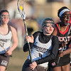 Mankato's Alexis Peterson (left) drives towards the goal and past Rochester John Marshall's Alek Agoth during Thursday's lacrosse game played at Dakota Meadows. Mankato defeated the Rockets 12-7. Photo by Jackson Forderer