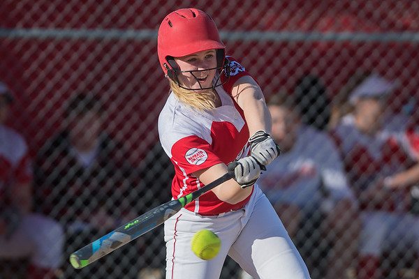 Mankato West's Briggs Carlson connects with the ball during the Scarlets game against Austin on Thursday. The Scarlets broke a 3-3 tie and rallied to win 7-5. Photo by Jackson Forderer
