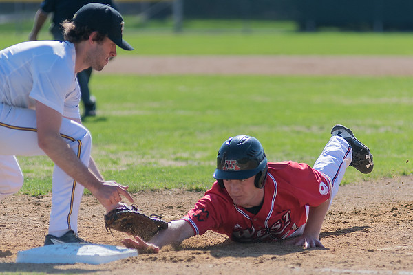 Mankato West's Clay Herding is tagged out at first base by Mankato East's Jackson Keller during a pick off play in Thursday's game. Photo by Jackson Forderer