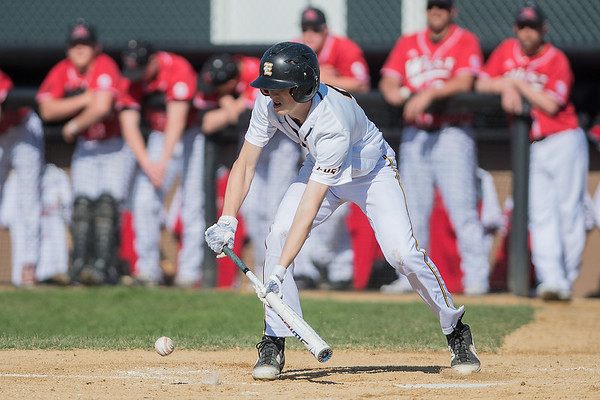 Mankato East's Logan Hermer gets low for a sacrifice bunt during Thursday's game against Mankato West. Photo by Jackson Forderer