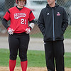 Bethany Lutheran assistant softball coach Eric Lewis talks to Anna Pipenhagen (21) after she reached first base in a game against Crown College on Thursday. Photo by Jackson Forderer