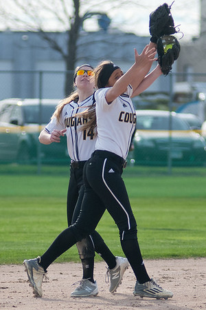 Mankato East's Lily Andrego (right) and Haley Stockman (14) collide while chasing down an infield fly ball in the Cougars game against Cretin-Derham Hall. The Mankato East Invitational softball tournament was held on Friday and continues today at Caswell Park. Photo by Jackson Forderer