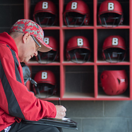 Bethany Lutheran head softball coach Dan Nessler writes a note in the dugout following a game against Crown College on Thursday. Photo by Jackson Forderer